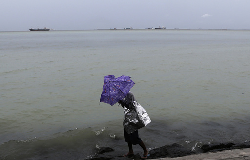 Wind brought by Tropical storm Rumbia blows a man's umbrella while walking along a seawall in Roxas Boulevard in Manila