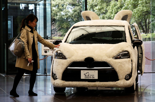 A woman touches Toyota's vehicle decorated as shape of dog at its headquarters in Tokyo