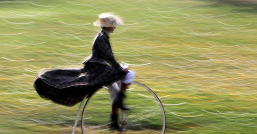 A participant wearing historical costume rides her high-wheel bicycle before the annual penny farthing race in Prague
