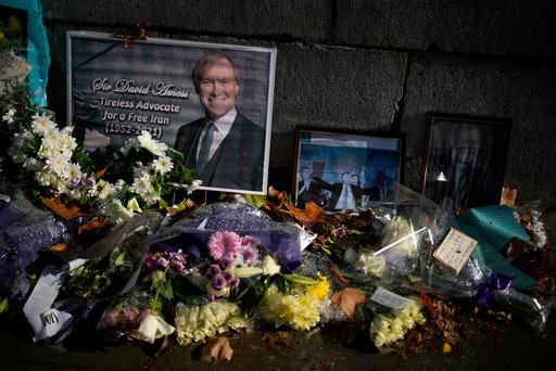 Blomster er lagt ned utenfor parlamentsbygningene i London til minne om David Amess. Foto: Matt Dunham / AP / NTB
