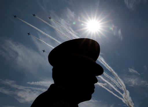 Japanese Self-Defence Forces' (SDF) official is silhouetted while flights performs air show during the annual SDF ceremony at Asaka Base