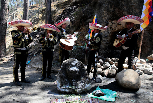 A Mariachi group performs in honor of a stone which bears an impression that locals refer to as Devil face, as a shrine frequented by indigenous witch doctors was removed to expand a main highway between La Paz and El Alto