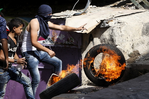 Palestinian pushes a burning tyre during clashes with Israeli troops in the occupied West Bank city of Hebron