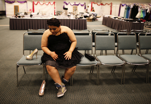 Elemmar Valle, 15, tries on a dress and shoes for her graduation dance at the Glamour Gowns event in Los Angeles