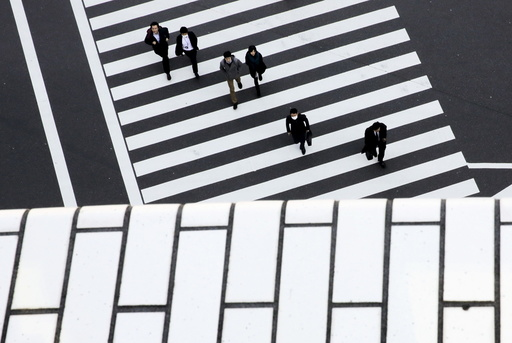 People cross a street in a business district in Tokyo