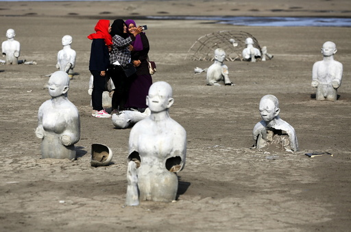 Women take pictures between stone sculptures of half-buried people at the Lapindo mud field in Sidoarjo