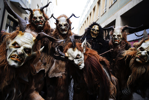 Men dressed as 'Krampuss' prepare to parade at Munich's Christmas market