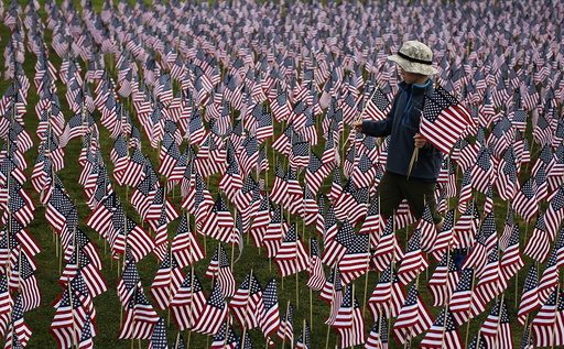 A boy walks among some of the 3,000 flags placed in memory of the lives lost in the September 11, 2001 attacks, at a park in Winnetka