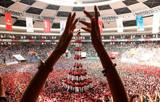 Colla Vella Xiquets de Valls form a human tower called castell, while a supporter applauds, during a biannual competition in Tarragona