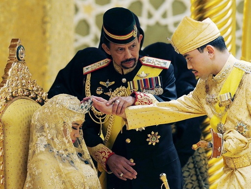 Brunei's Sultan Hassanal Bolkiah holds the arm of his son Prince Abdul Malik to bless Malik's new wife Dayangku Raabi'atul 'Adawiyyah Pengiran Haji Bolkiah during the enthronement ceremony at their wedding in Bandar Seri Begawan