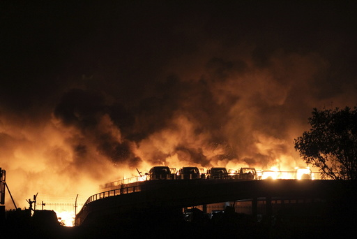 Vehicles are seen burning after blasts at Binhai new district in Tianjin municipality