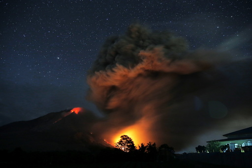 Hot lava flows from Mount Sinabung volcano during eruption as seen from Tiga Serangkai village in Karo Regency