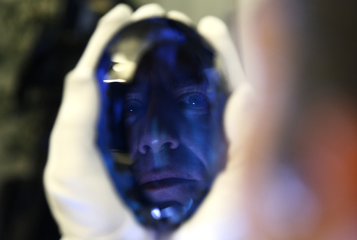 Philanthropist Maurice Ostro is reflected in his Ostro stone, the largest known blue topaz stone, as he holds it for media at the Natural History Museum in London