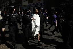 En demonstrant som ropte «Redd planeten», ble ført bort av politiet etter at de hadde dekket til overkroppen hennes utenfor Windsor Castle lørdag. Foto: Matt Dunham / AP / NTB