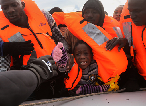 A child reacts among migrants as they try to reach a rescue craft from their overcrowded raft, while lifeguards from the Spanish NGO Proactiva Open Arms rescue all on aboard, in the central Mediterranean Sea
