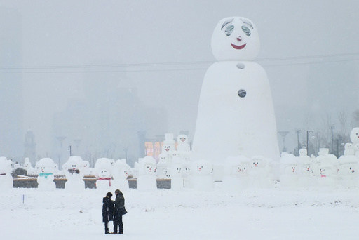 People are seen next to a giant snowman at a park in Harbin