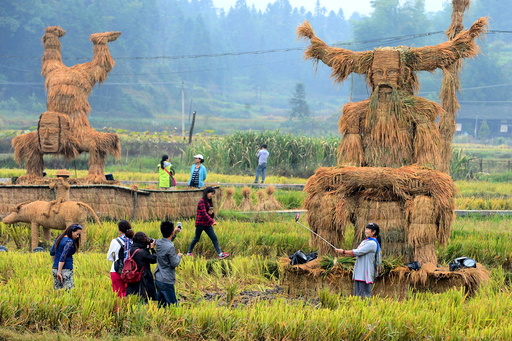 Tourists take pictures of straw figurines of traditional deities Shennong and Zhang Wulang during China's National Day Holiday, in Xinhua county