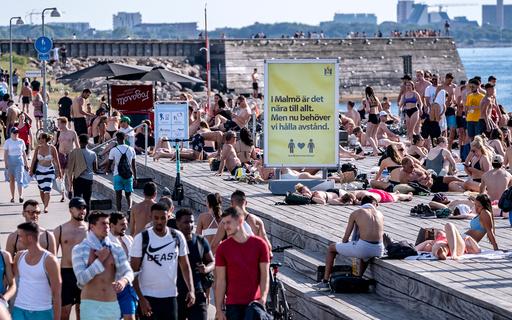 Et skilt med oppfordring til å holde avstand står midt blant folk i Malmö. Det siste døgnet er x personer registrert døde som følge av koronaviruset i Sverige. Foto: Johan Nilsson / TT / NTB scanpix