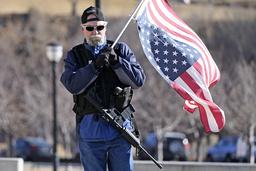 En og annen tilhenger av avtroppende president Donald Trump, som denne væpnede mannen utenfor kongressbygningen i Salt Lake City, protesterte onsdag mot innsettelsen av demokraten Joe Biden som president. Foto: AP / NTB