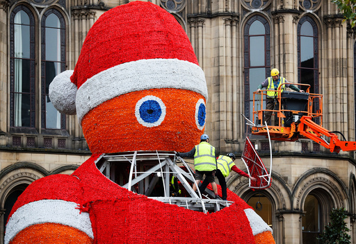 Workers install a giant Santa Claus figure in Manchester