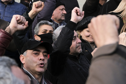 Opposition demonstrators shout anti-government slogans as they rally to pressure Armenian Prime Minister Nikol Pashinyan to resign in the center of Yerevan, Armenia, Thursday, Feb. 25, 2021. Armenia's prime minister has spoken of an attempted military coup after facing the military's General Staff demand to step down. The developments come after months of protests sparked by the nation's defeat in the Nagorno-Karabakh conflict with Azerbaijan. (Hrant Khachatryan/PAN Photo via AP)
