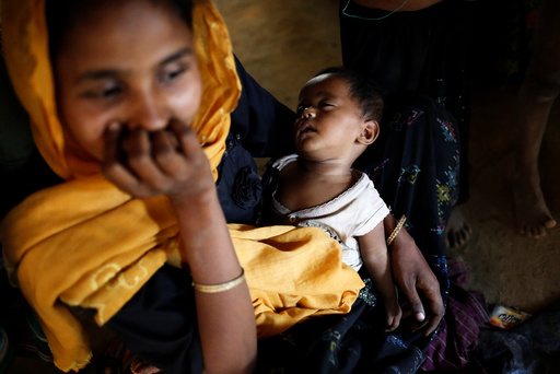 A Rohingya child sleeps on mother's lap inside their house, at Balukhali Makeshift Refugee Camp
