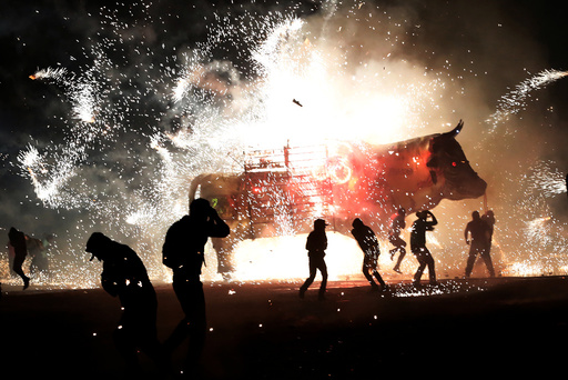 People enjoy fireworks exploding from a traditional bull known as