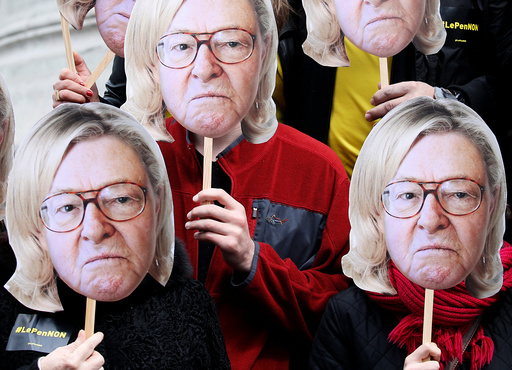 Activists wear masks depicting the face of Jean-Marie Le Pen, the founder of the French far-right National Front, with the hair of his daughter Marine Le Pen during a demonstration as part of traditional May Day labour day march in Paris