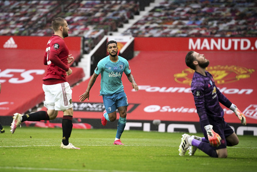 Bournemouth's Joshua King, center, reacts after scoring a penalty kick goal on Manchester United's goalkeeper David de Gea, right, during the English Premier League soccer match between Manchester United and Bournemouth at Old Trafford stadium in Manchester, England, Saturday, July 4, 2020. (Dave Thompson/Pool via AP)