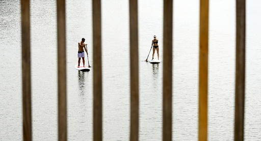A couple, seen through a bridge railings, beat the heat by taking to the water to paddle board along the Potomac River in Washington