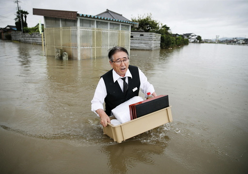 A man holding a tray of belongings wades through a road at an area flooded by the Omoigawa river, caused by typhoon Etau in Oyama