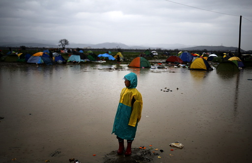 A migrant boy stands near a flooded muddy field as it rains at a makeshift camp on the Greek-Macedonian border, near the village of Idomeni