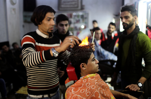 Palestinian barber uses fire to straighten the hair of a customer in Rafah in the southern Gaza Strip