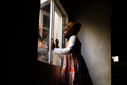Haitian migrants talk through a window at an Evangelical Church, being used as a shelter for stranded immigrants on their way to the U.S., in Tijuana