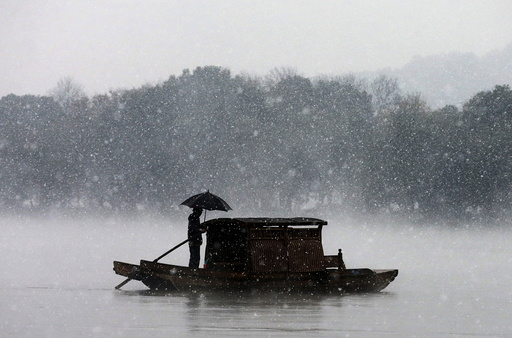 A man holds an umbrella to shield against snowfall as he rows a boat on the West Lake in Hangzhou