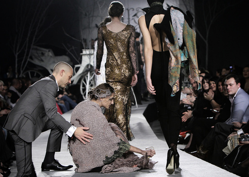 A model is helped by a spectator after she fell while presenting a creation by Georgian designer Irakli Nasidze during Georgian Fashion Week in Tbilisi