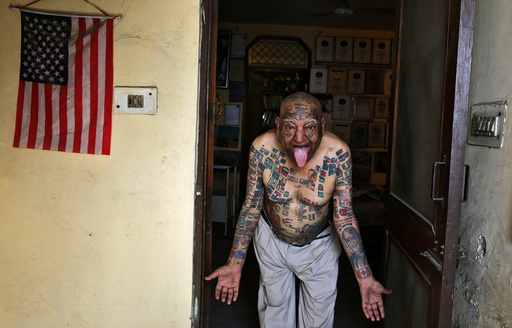 Guinness Rishi, multiple world record holder including most flags tattooed on his body, poses for a photograph outside his apartment in New Delhi
