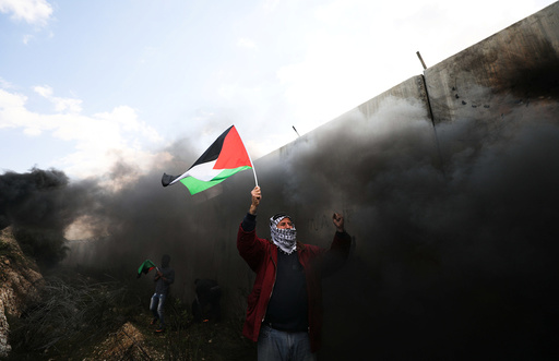 Protester holds a Palestinian flag during clashes with Israeli troops at a protest marking the 12th anniversary of a campaign against the Israeli barrier, in the West Bank village of Bilin near Ramallah