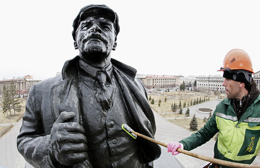 A worker washes a statue of the Soviet state founder Vladimir Lenin on the eve of his birth anniversary in Krasnoyarsk
