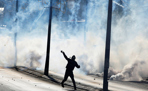 A Palestinian protester hurls stones as tear gas is fired by Israeli troops during clashes in the West Bank city of Bethlehem