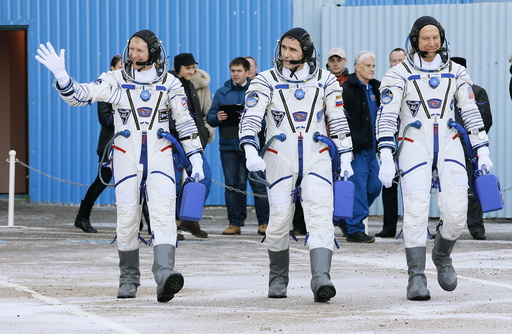 Members of the main crew of the expedition to the International Space Station (ISS), walk to report to members of the State Committee prior the launch of Soyuz TMA-19M space ship at the Russian leased Baikonur cosmodrome, Kazakhstan