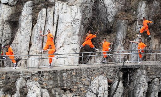 Students from a martial art school practice Shaolin Kung Fu on cliffs at Songshan Mountain in Dengfeng