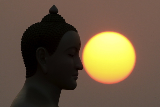 The sun rises next to a Buddha statue while monks and novices gather to receive alms at Wat Phra Dhammakaya temple, in what organizers said was a meeting of over 100,000 monks in Pathum Thani