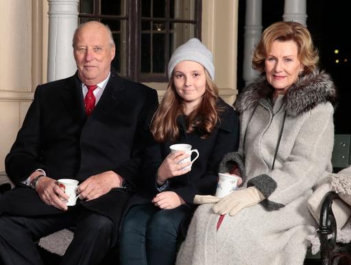 Kong Harald, prinsesse Ingrid Alexandra og dronning Sonja drikker gløgg av kopper prinsesse Astrid har malt og spiser pepperkaker utenfor lysthuset på Slottet i forbindelse med julefotografering tirsdag ettermiddag.
