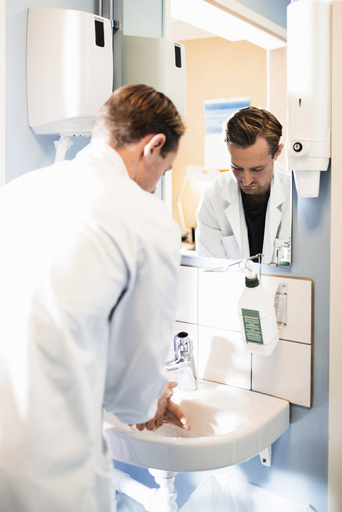 Rear view of male doctor washing hands in bathroom