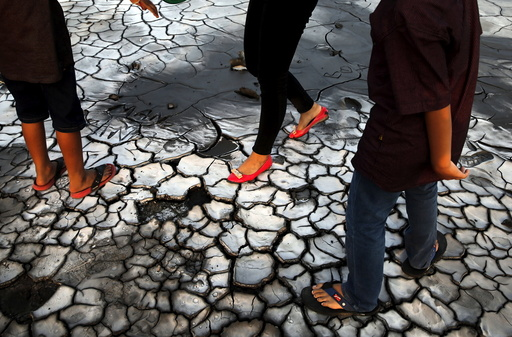 Tourists walk on dried mud at the Lapindo mud field in Sidoarjo