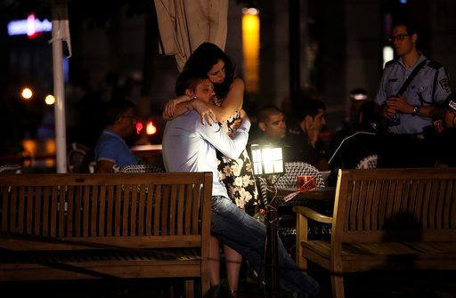 People hug each other following a shooting attack that took place in the center of Tel Aviv