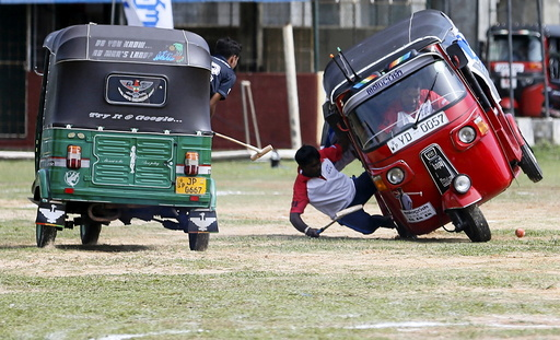 A competitor falls out from his three-wheeled vehicle during a
