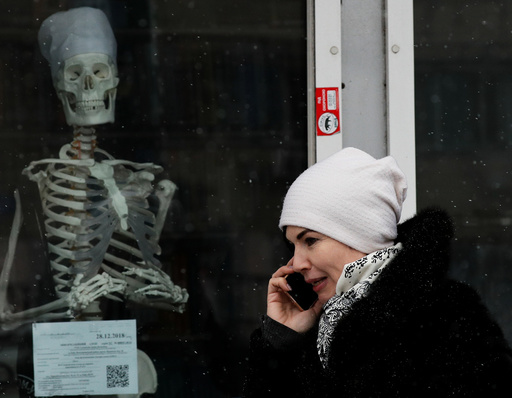 A woman walks past the window of a medical store in Kiev