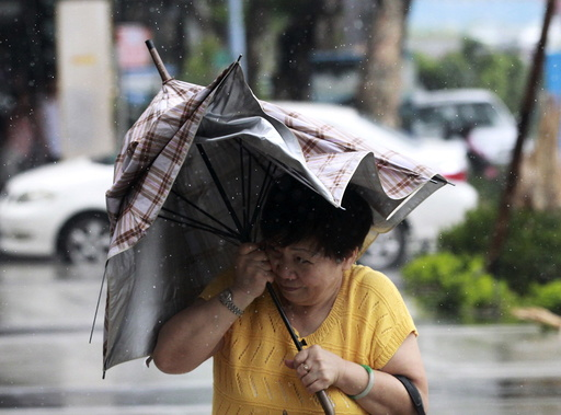 A woman holds her umbrella while walking against strong winds as Typhoon Soudelor hits Taipei